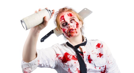 A woman in zombie make up with a spray can spraying a halloween message photo
