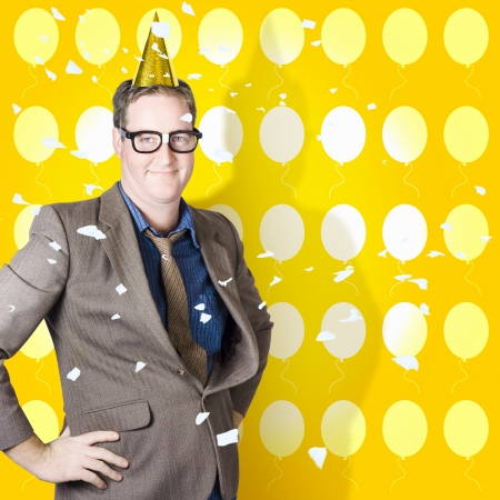 Winning businessman celebrating a great victory in party hat with falling decorations and balloons. Business success photo