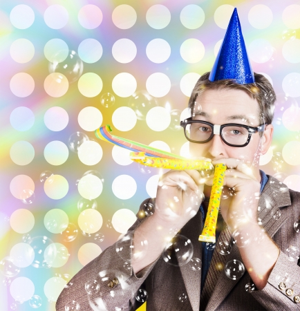 Bright and vibrant photograph of a nerd man in glittering party hat celebrating a birthday bash with a puff of noise and bubbles. Fun times photo