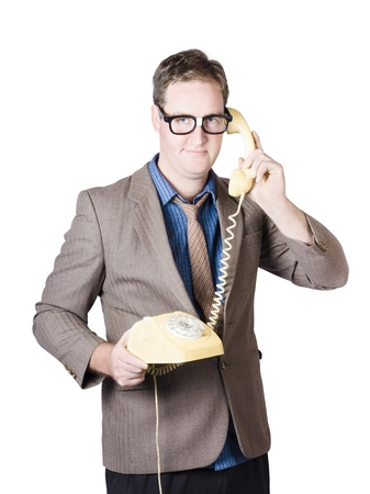 Comical businessman holding corporate talk when dialling in on a 1950s yellow retro telephone Stock Photo - 20043737
