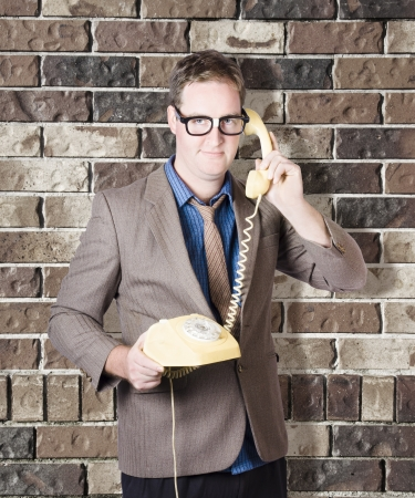 Humorous male nerd engaging in business chatter on phone with discussions of retro revival. Brick wall background photo