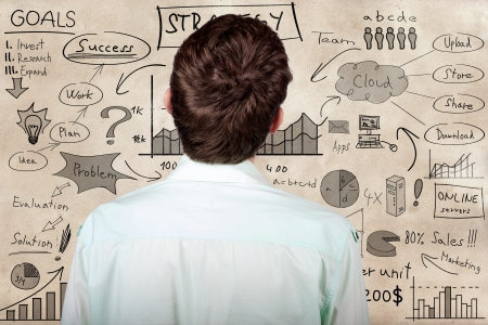 Creative businessman looking to develop innovative business plan when looking to hand drawn marketing illustration on a texture wall illustration