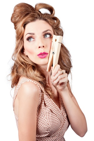 Quirky photo of a pretty pinup housewife wearing pink lipstick with big fifties hairdo, holding large cleaning peg on white background photo