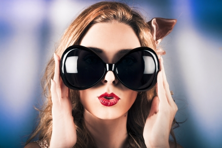 Cute fashion portrait on the face of a surprised pinup girl wearing funny retro sunglasses with bright red lipstick photo
