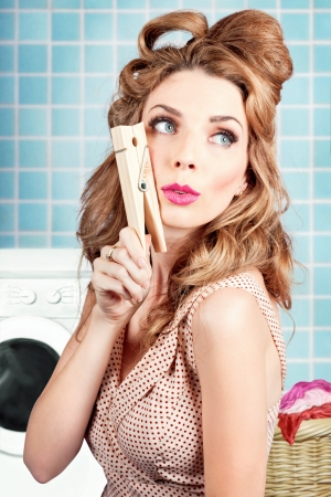 Gorgeous pin-up woman holding large cleaning peg in home laundry. Choirs and housework photo