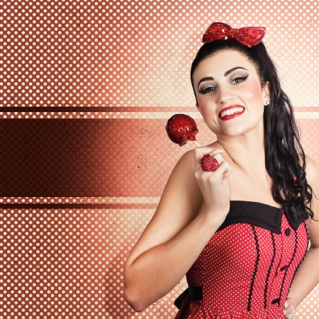 Polka dot portrait of a beautiful sweet candy pinup girl wearing cute hair bow and holding a toffee apple. Vintage design background photo