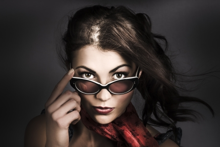 Dark fashion portrait of a beautiful and mysterious young woman with windblown brunette hair and 50s makeup wearing pinup sunglasses photo
