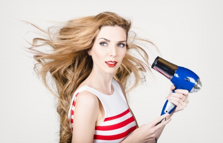 Closeup portrait of a beautiful woman with long chestnut red straight hair holding hairdryer. fashion studio portrait Stock Photo - 20443398