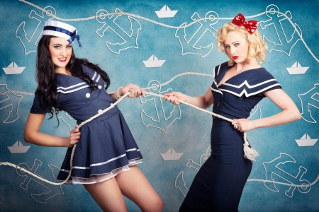Cute retro portrait of two beautiful navy pinup girls wearing sailor uniforms pulling on a tug of war rope when personal training for elite fitness. Anchor and boat design background photo
