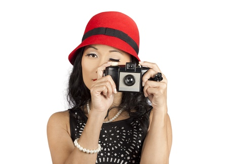 Cute pin up Asian lady adjusting aperture while taking photo on old fashioned film camera. Setting the capture photo