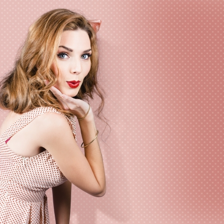 Beautiful girl expressing pretty smile in pinup style on pink dot background photo