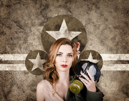 Vintage WW2 portrait of a sombre 1950s pinup woman holding army gas mask when stopping to pay tribute to the fallen. Memorial day concept photo