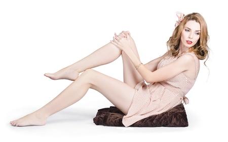 Soft fashion model. Full body portrait of an elegant woman posing in retro fashion on throw rug. Over white background Stock Photo - 20680164