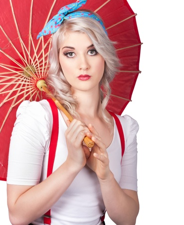 Old fashioned picture of a dreamy blond pin up woman wearing cute red suspenders holding red parasol photo