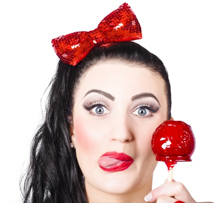 Funny closeup portrait on the face of a sweet pin-up girl eating a candy toffee apple with a cheeky expression over white background photo