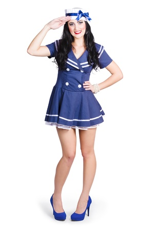 British navy blue pin up girl standing to attention in sailor uniform while saluting photo