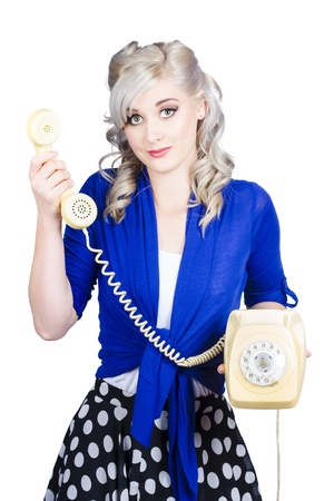 Attractive blond female secretary handing over the receiver on vintage yellow phone, its for you photo