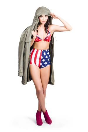 American army pinup girl wearing general war jacket, saluting the stars and stripes. USA patriot photo