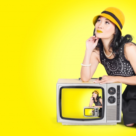 Photo of a beautiful vogue girl striking a pose on a vintage tv set in 50s fashion style on yellow background photo