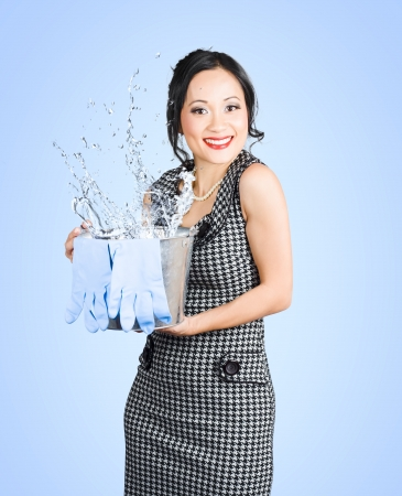 Portrait of an attractive young woman making a splash while holding cleaning equipment photo