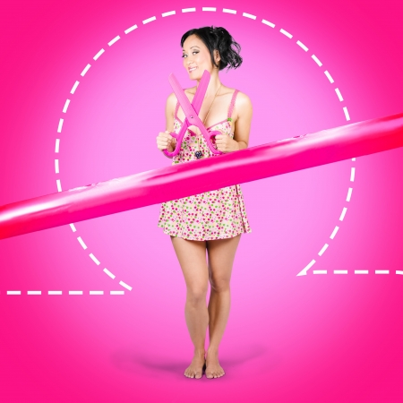 Attractive young hair salon woman standing by pink ribbon with scissors. Beauty product sale Stock Photo - 20998652