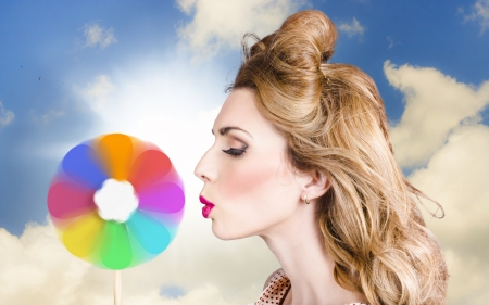Beauty portrait of a beautiful makeup girl blowing on a colors palette wheel. Hair and cosmetics coloring concept photo