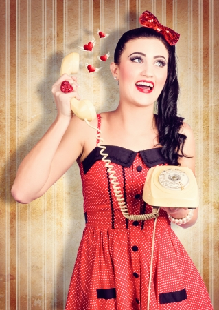 Grunge photograph of a smiling beautiful pinup woman talking about love on a retro phone. Love heart butterflies photo