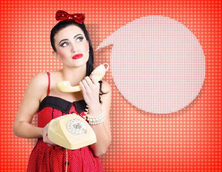 Comic portrait of a young beautiful brunette lady chatting on the phone into a retro clip art speech bubble. Polka-dot design background photo
