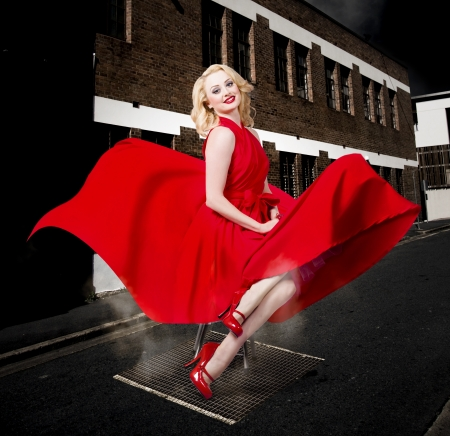 Blond Marilyn Monroe pinup girl doing a sexy red dress dance underneath an open street vent. Classical fashion styles.  photo