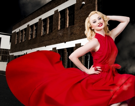 Portrait of a beautiful sexy blond girl wearing a long elegant red dress when dancing in a urban back alley with stylish hair and make up photo