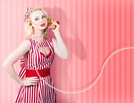 Comic retro photo of a housewife in 1950s fashion style gossiping on a vintage banana phone photo