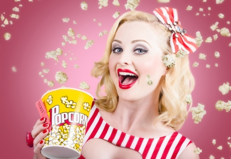 Retro photograph of a beautiful vintage girl with surprise expression watching premier film at movie theater amongst raining popcorn. Classic movies concept photo