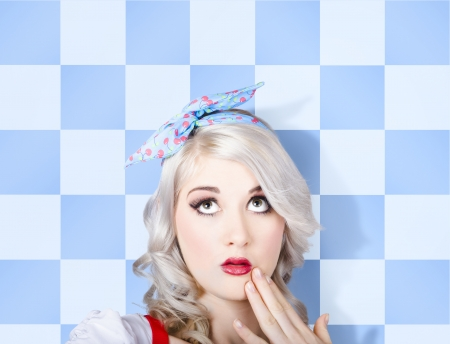 Close-up photo on the surprised face of a young stylish caucasian pinup woman wearing flawless make-up looking up to cosmetic copy space. retro styling photo