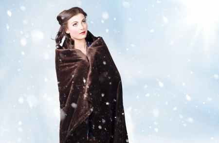 Attractive young winter girl standing outdoor in the snow wrapped in blanket. Cold copyspace on wintertime background photo