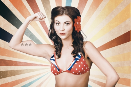 Vintage photo of beautiful pinup girl with american star tattoo showing the power of womens rights when flexing muscles in retro fashion style photo