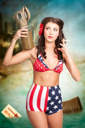 Grunge portrait of a beautiful military pin up woman removing gas mask on war torn beach to inhale smoke. American danger woman photo
