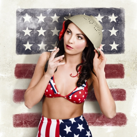 USA pin-up woman smoking cigarette on united states flag wall wearing army green colander helmet and American costume. Womens support for World War II soldiers. photo