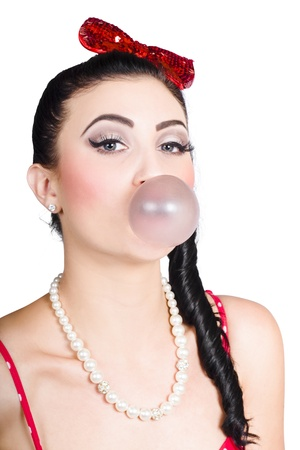 Retro portrait of sweet vintage pin up woman wearing pearl necklace blowing bubble gum, on white background photo