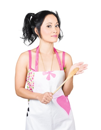 Isolated picture of a young woman holding wooden spoon while cooking at home  photo