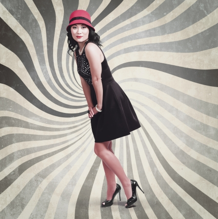 Glamour full length portrait of a young beautiful asian woman posing in red hat on vintage swirl background. Retro styling Stock Photo - 21496230