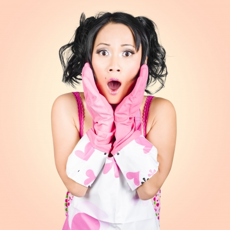 Funny portrait of stressed young housewife gasping in shock horror wearing washing gloves photo
