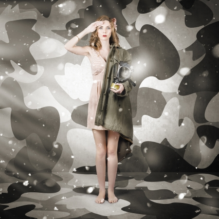 Sexy army girl saluting on snow camouflage background. Winter fashion photo