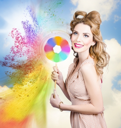 Beauty portrait. Pretty girl holding toy spraying colored paint in a hair and makeup coloring concept  photo