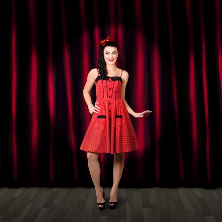 Dancing woman wearing retro rockabilly dress performing on a theatre stage in a depiction of cabaret beauty and glamour Stock Photo - 21577857