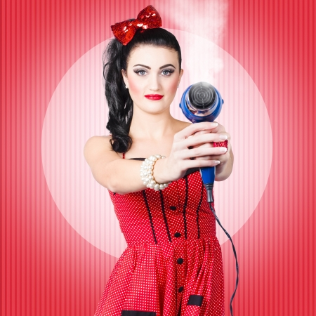 Portrait of a young beautiful pinup girl taking aim with hair dryer over retro red background. Hair care concept photo