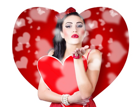 Beautiful girl in a bright love romance sending a kiss on creative hearts background photo