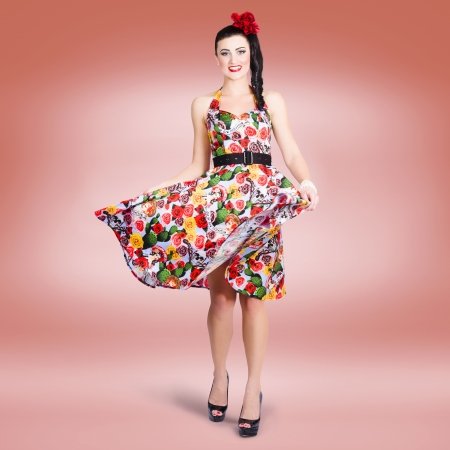 Smiling brunette beauty spinning around while wearing a colourful summer dress photo
