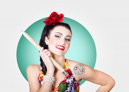Portrait of a beautiful rockabilly girl with stylish hair and make-up showing tattooed arm and tattoo stencilling pencil photo