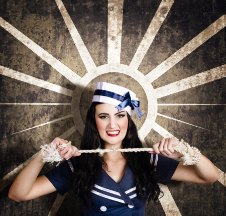 Sailor girl portrait. Beautiful young sexy woman breaking navy rope in retro makeup and hairstyle. Vintage design background photo