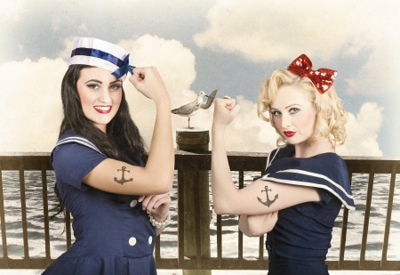 Artistic portrait of two sexy sailor pin up girls with anchor tattoos flexing muscles on a vintage pier promenade when competing in strength and conditioning exercises. Vintage pinup style photo